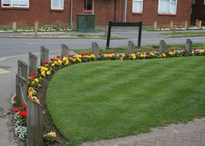A flower bed in full bloom edging a manicured grass area in the centre of Messingham