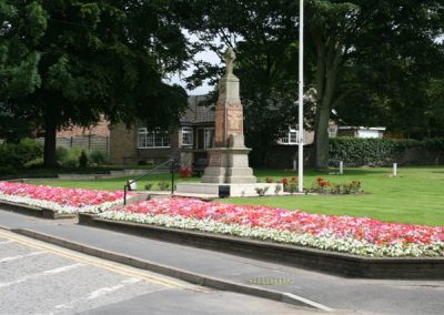 Flower beds in full bloom in the foreground of the Messingham War Memorial
