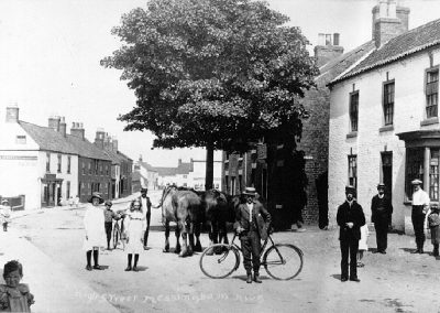 A vintage photograph showing Messingham High Street with a number of villagers milling about